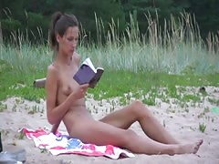 Girl showing her pussy, reading a book at a public beach